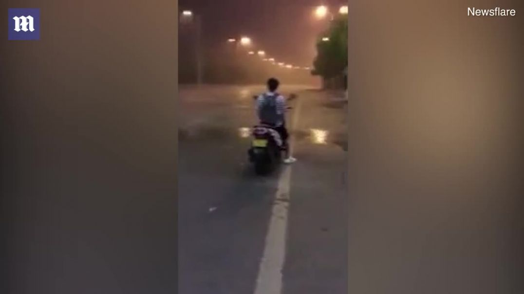 Bizarre footage shows a scooter rider staying dry as he waits just metres....